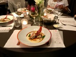 Monkfish Saltimbocca on a white plate on a restaurant dining table