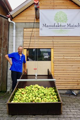 A man standing next to a slide full of pears