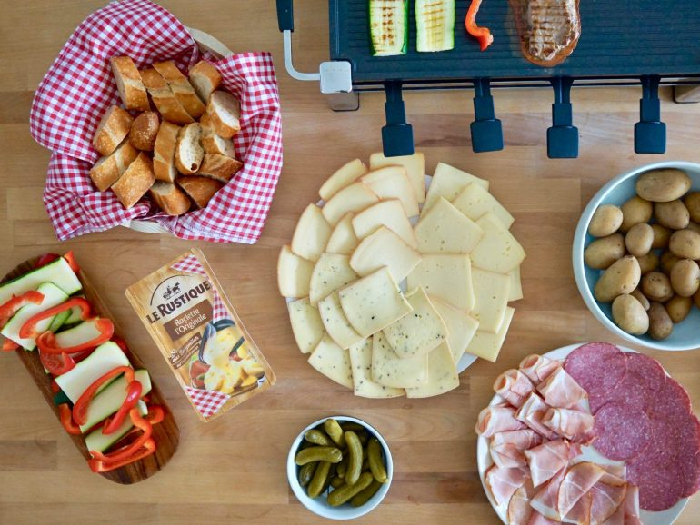 Flat lay of a table filled with plates of raclette cheese, meat, bread, silver onions and cornichons