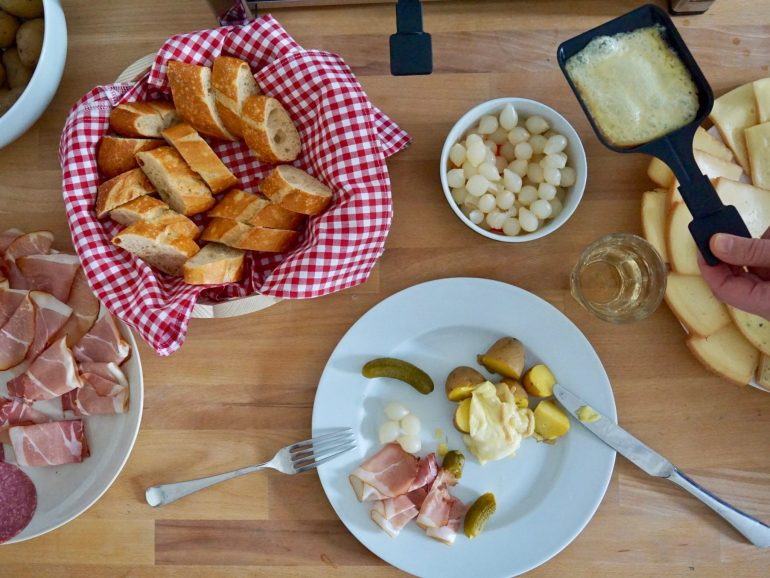 Flat lay of a plate of half eaten raclette cheese with potatoes, plus other dishes of food