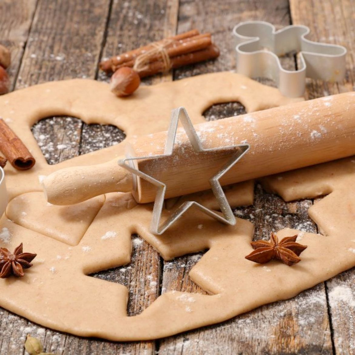 Christmas cookies being cut out with star-shaped cutter and a rolling pin