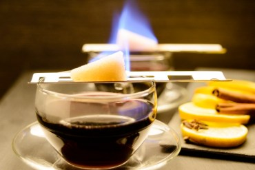 Two glasses of Feuerzangenbowle with sugar cubes melting on top