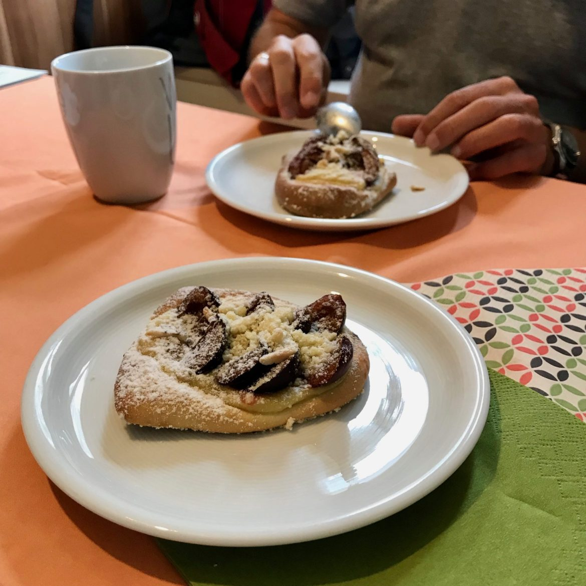 Two plates of German plum pastries, one being eaten