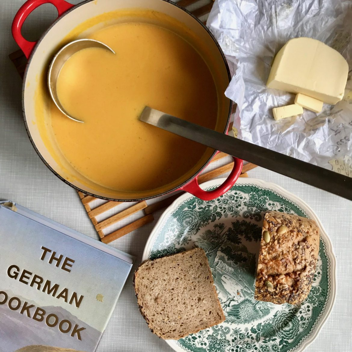 A flatlay of a pan of pumpkin soup, some sliced bread on a green and white plate, a pat of butter and a large cookbook