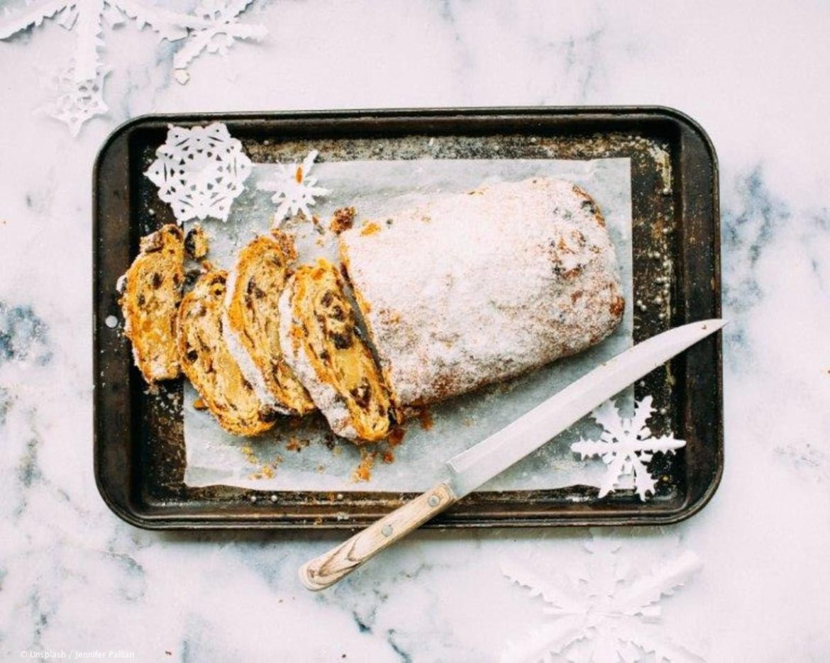 Sliced stollen on a baking tray with a long knife