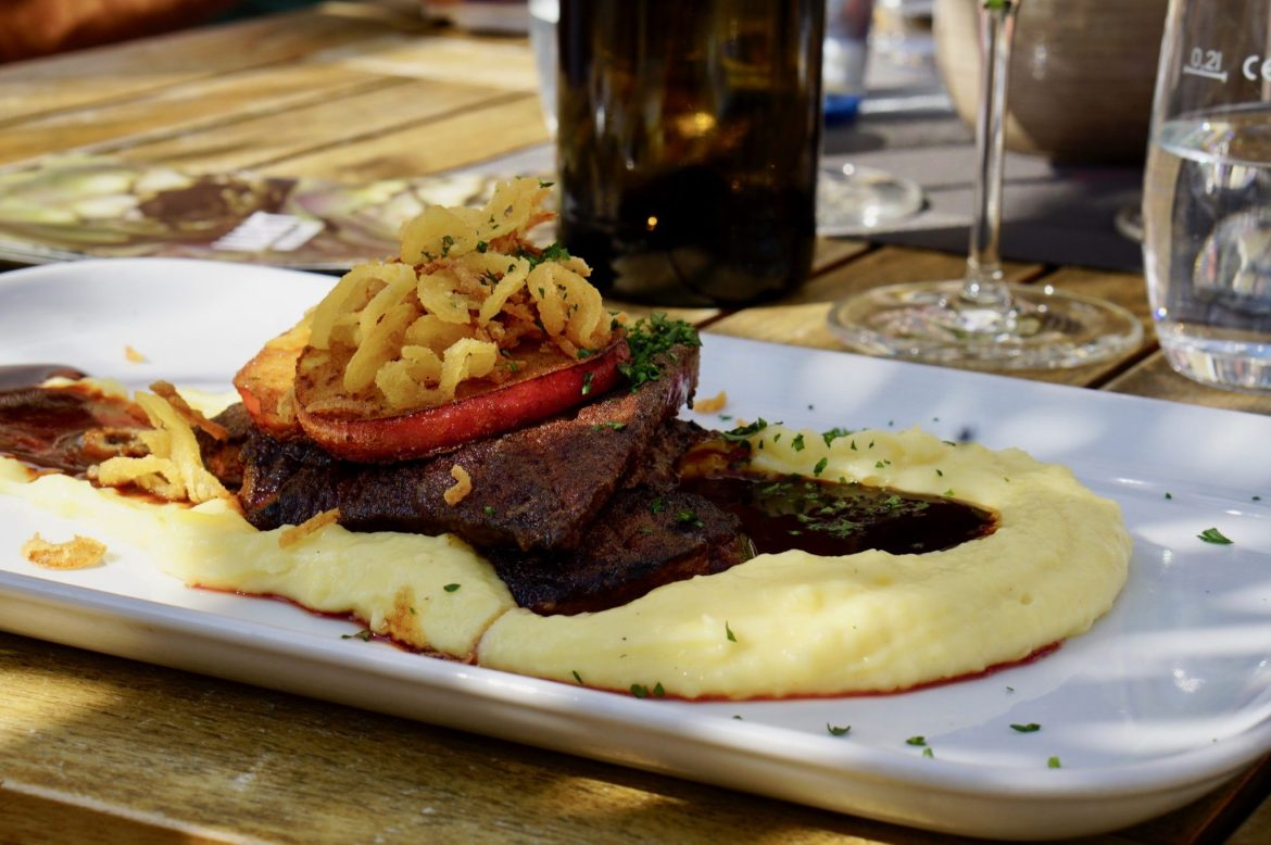 A rectangular plate of calves liver with mashed potatoes and onion rings