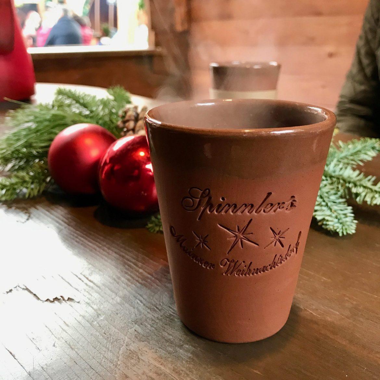 A terracotta mug of steaming mulled wine