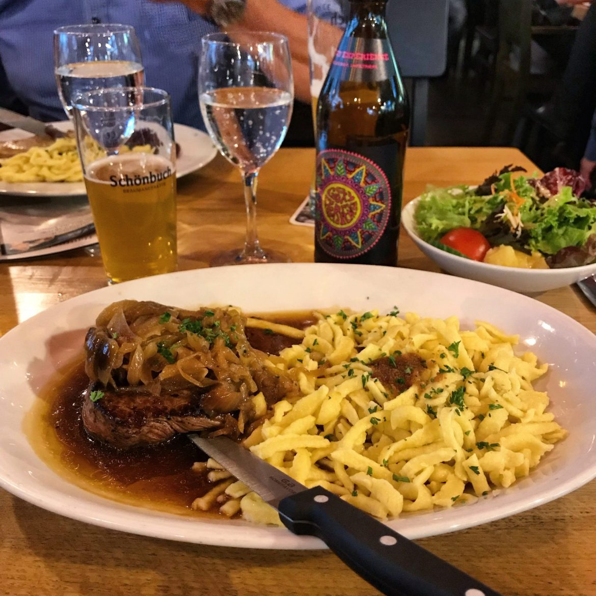 An oval white plate filled with steak, Spätzle, onions and gravy in front of some beers