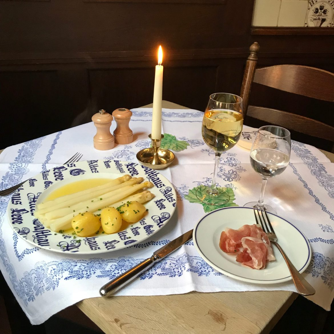 Plates of white asparagus, potatoes and ham on a wooden table