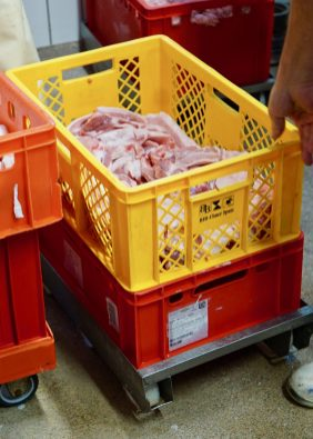 A yellow crate filled with pork belly stacked on a red crate