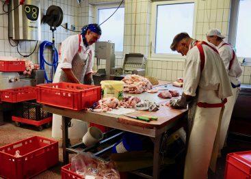 Three butchers preparing meat