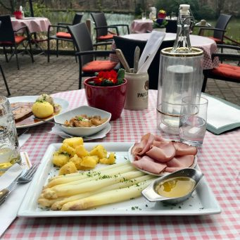 A red and white checked tablecloth table outside at a German restaurant with drinks and food on