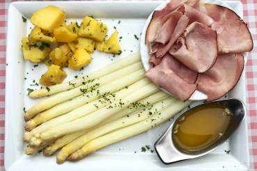 A rectangular white plate from above with white asparagus, ham, potatoes and a sauce boat of butter