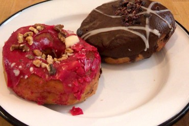 A pink and a brown donut on a white plate