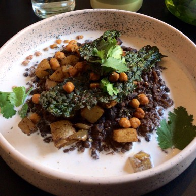 A shallow speckled white bowl filled with black lentils, chickpeas, sweet potato, cavolo nero and fresh coriander