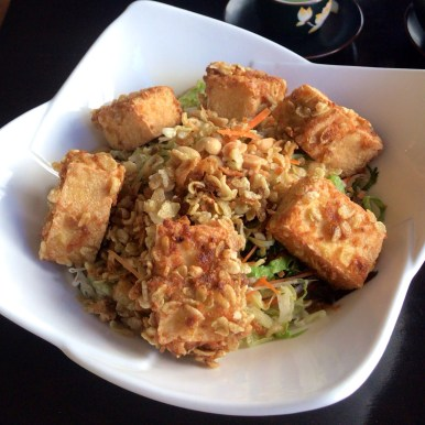 Crispy baked tofu with rice noodles and salad in a white bowl
