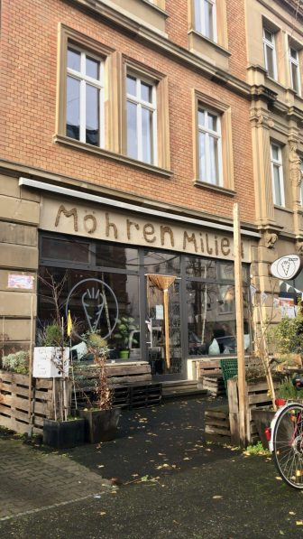 The front of a vegan cafe in Mainz with plants in crates outside