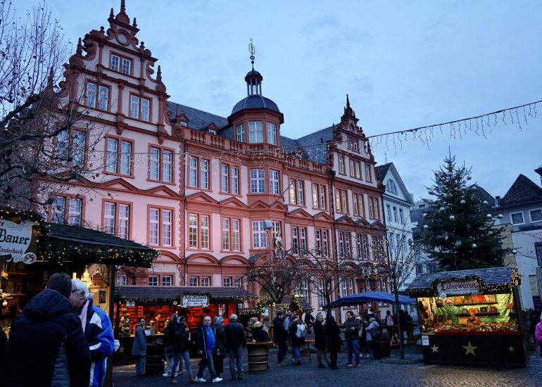 Pink Baroque building with Christmas market stalls and lights in front of it