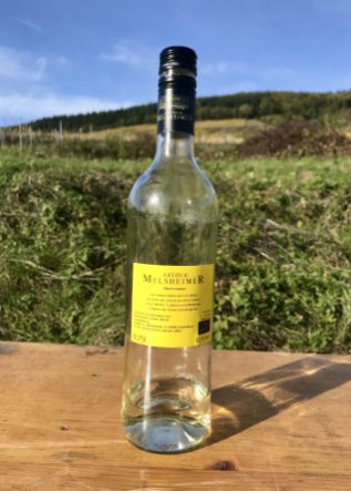 An almost empty bottle of white wine with a yellow label on a trestle table in a vineyard