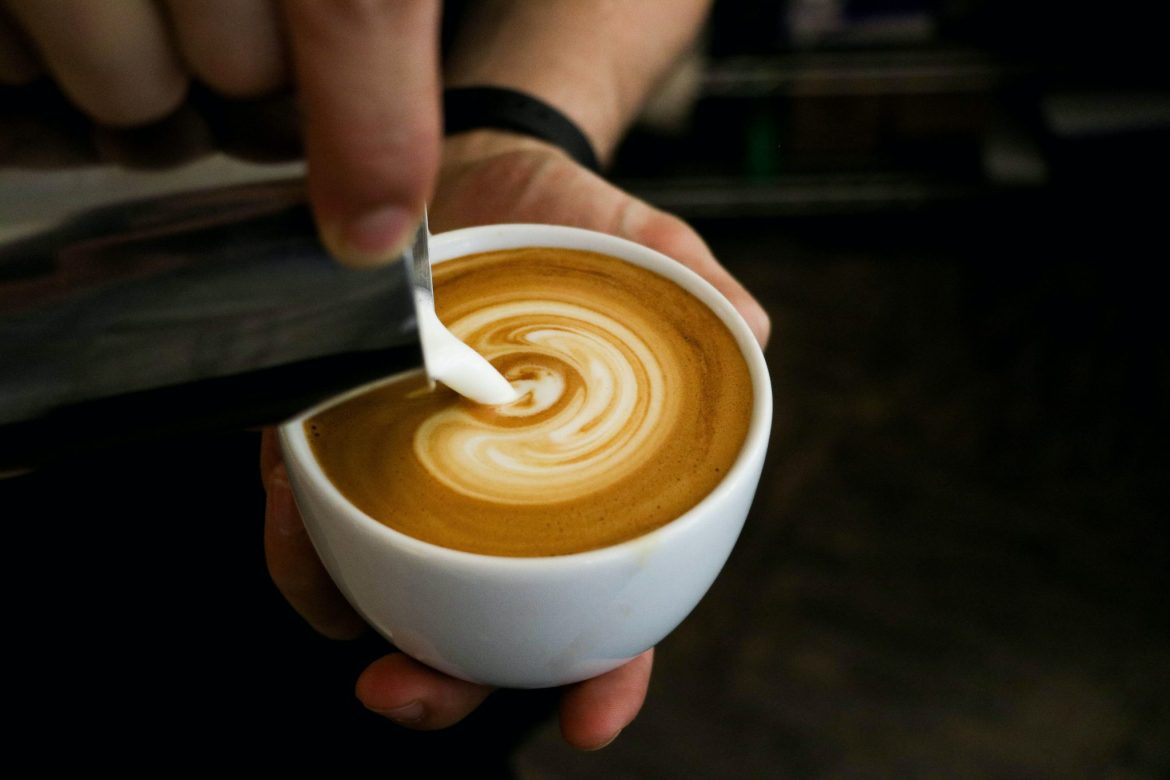 Cream being poured into a cup of coffee