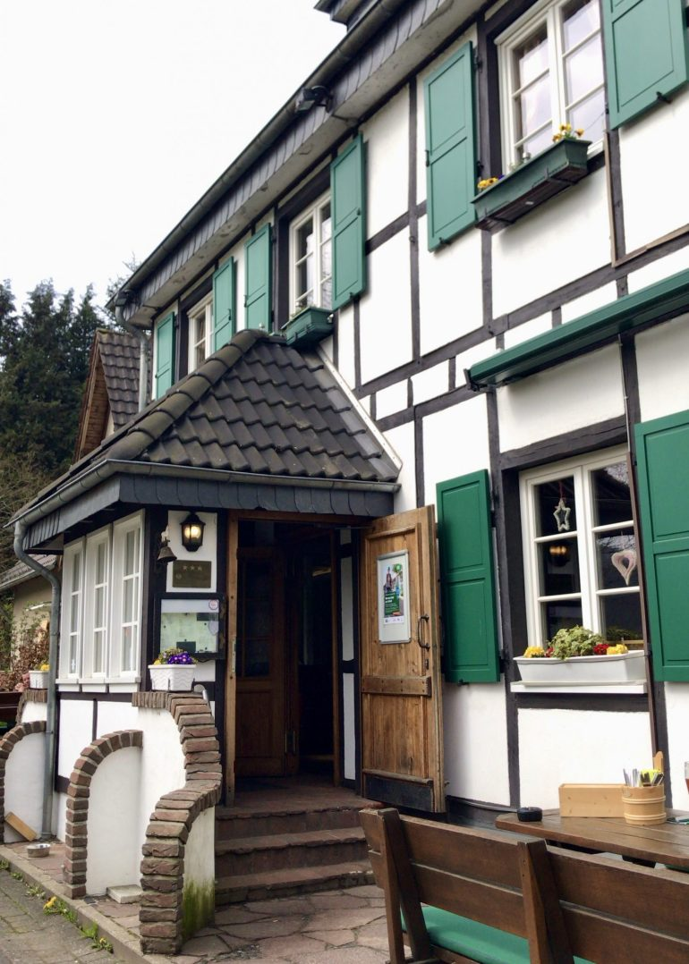 The outside of Hotel-Restaurant Wisskirchen with green shutters and half-timbered wood details
