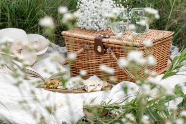 A picnic blanket with hamper and food laid out amongst tall grass