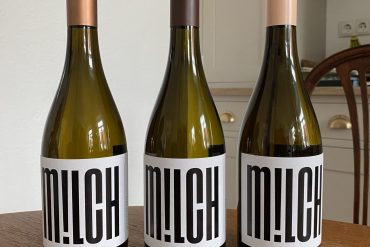 Three bottles of M!LCH wine on a wooden table in a kitchen