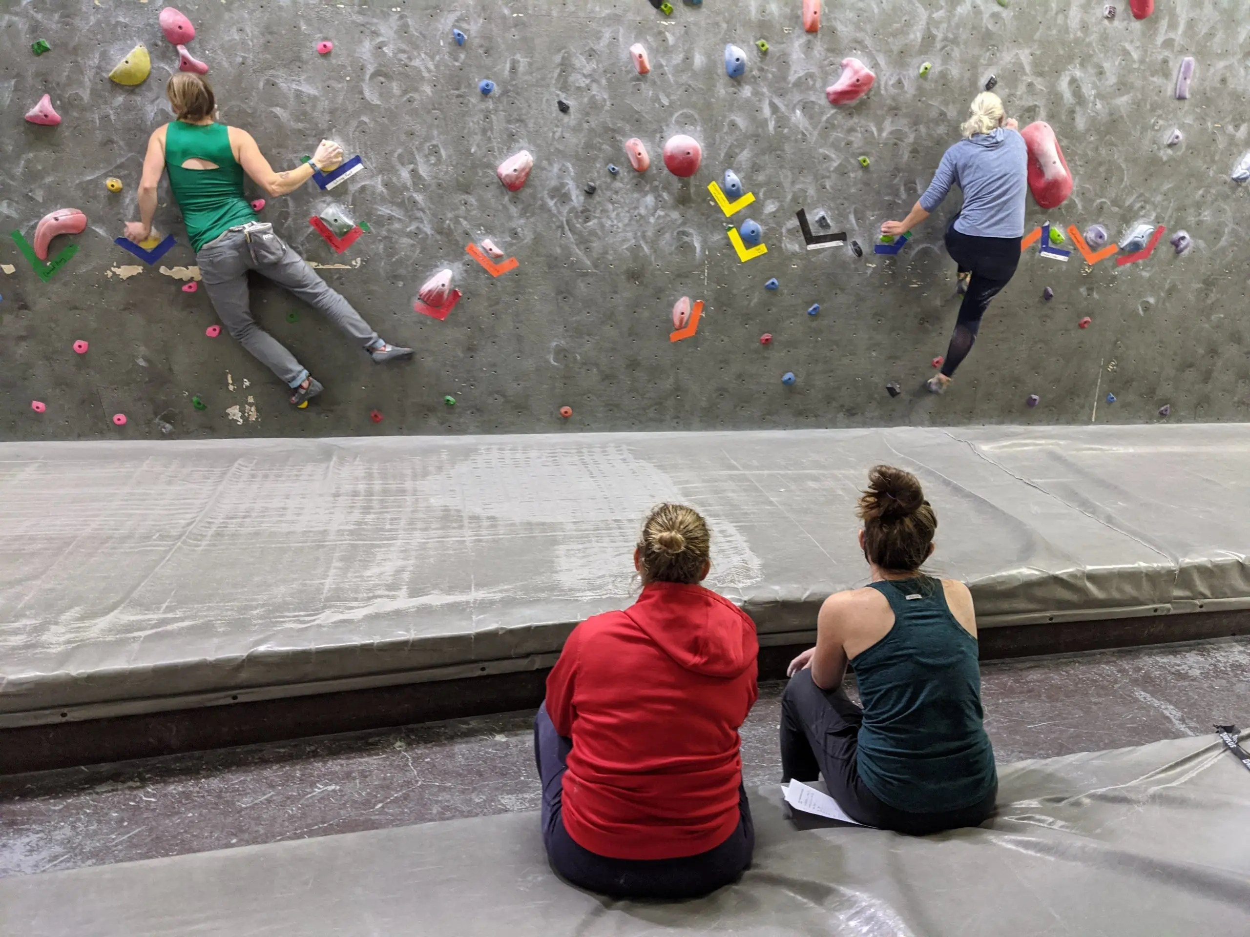 two climbers climbing at night league