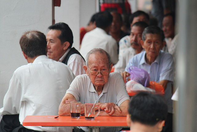 An elderly man eating at a table in Central Singapore