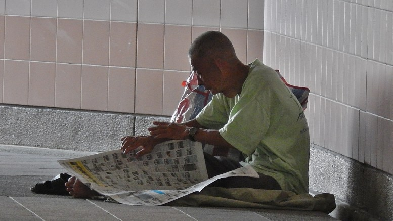 A homeless man reads a newspaper on the ground in Central Singapore