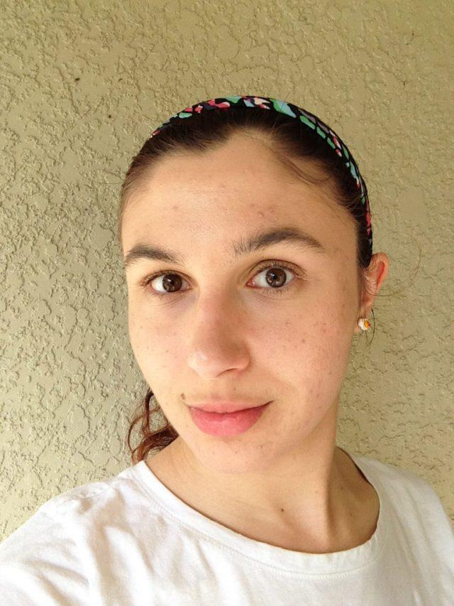 Ashlee Craft wearing a white t-shirt, cute kawaii egg earrings, & multicolored headband