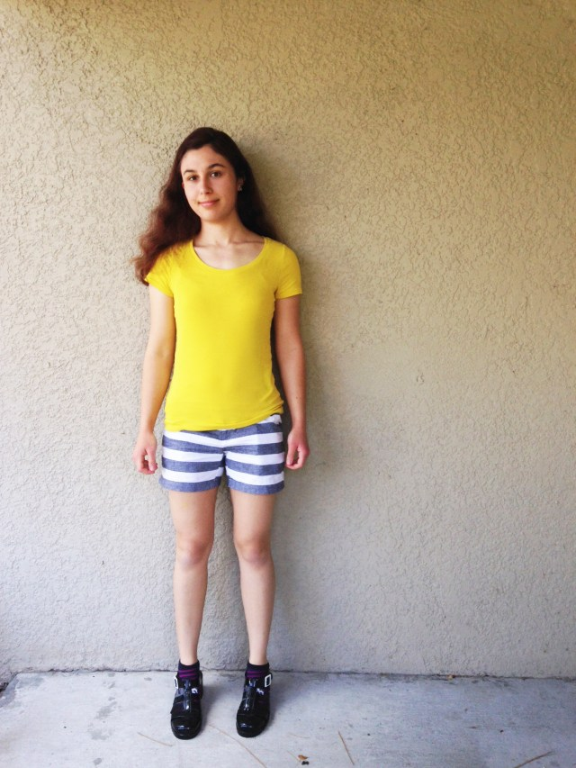 Ashlee Craft wearing black heeled jelly shoes, sloth socks, striped shorts, & a yellow shirt