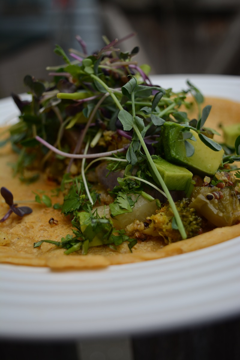 Chickpea socca with avocadoes, microgreens, roasted vegetables and fresh herbs