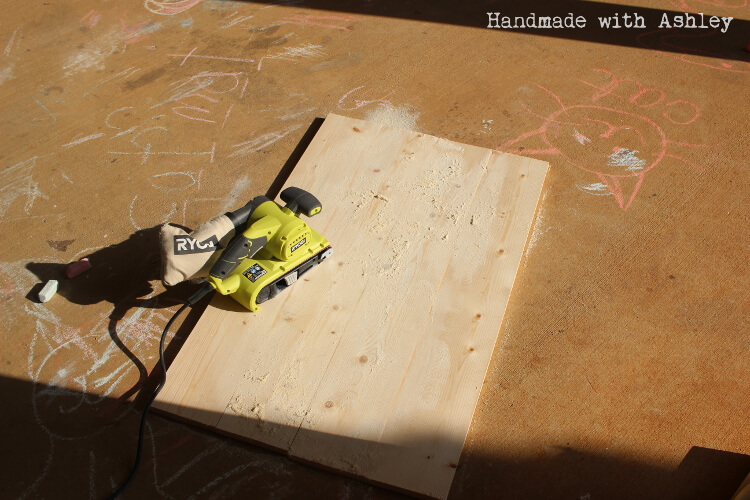 Sanding the surface of the panel with a Ryobi Belt Sander