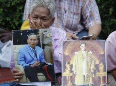 Donna con ritratti di re Bhumibol Adulyadej fuori dall'ospedale di Bangkok in cui è ricoverato Foto Rungroj Yongrit EFE