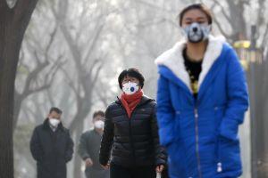 Cina, smog record: parco Ritan di Pechino tutti indossano la mascherina. 19 dicembre 2016. Foto Andy Wong/AP