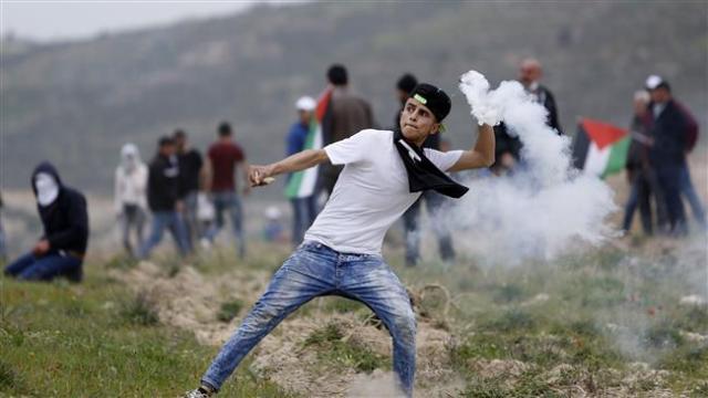 Ragazzo palestinese rilancia indietro un gas lacrimogeno ancora fumante contro dei soldati israeliani.