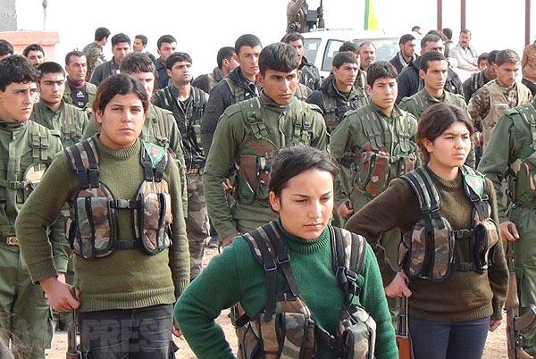 内戦前から、若者たちの中にはPKKのゲリラに参加する者があとを絶たず、トルコ軍との戦闘などで相当数の戦死者を出す町でもあった。ゲリラ戦闘員には組織名がつけられるが、出身地をつける場合が多い。アハマド・コバニやシルワン・コバニなど「コバニ」を冠した名前がたくさんあるのはこの町から多くの若者がゲリラとなったことを意味する。シリアが内戦に陥ると、彼らが地元青年を訓練し、人民防衛隊(YPG)を編成した。写真は町の守りを固めるYPG戦闘員。イスラム勢力との対決を女性解放闘争とも位置づけており、共産主義的影響も垣間見える。(2014年1月撮影)