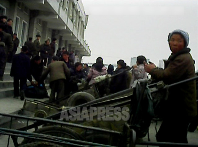 リアカー引きの女性が客待ちをしている。2013年3月平安南道の平城駅前(アジアプレス)