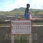 "A signboard put up in Changbai County, in a town on the Chinese border upstream on the Amrok-gang(Yalu River). The signboard says ""We must crack down firmly on trading of poison (drugs) and smuggling"". Changbai County is across the river from Hyesan City, Ryanggang Province/North Korea, and is one of the most busy areas for smuggling. (1999 Jilin Province/China - Photo by ISHIMARU Jiro) ASIAPRESS"