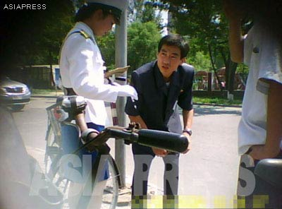 A policewoman issues a man a traffic ticket. Many citizens who do not want to pay for a ticket try to bribe the officers for a lesser amount of money. Working as a traffic officer is known to be lucrative, and for this reason policewomen must secure their positions through connections to ranked officials.[Gu Gwang-ho, 2011]