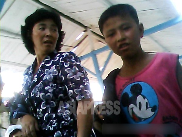 A young man in an Mickey Mouse T-shirt walking through a market. He risks being detained by the anti-socialist activities inspection unit. Taken by team Mindulle at a market place of Hyesan City, Ryanggang Province on August 2013. (ASIAPRESS)