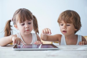 Two small kids using a tablet