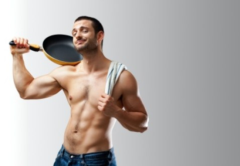 A handsome muscular cook posing with a pan on his shoulder on a neutral background with space for text