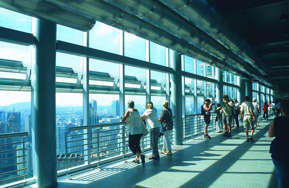 Tourist Enjoying View From Inside Skybridge Petronas Towers