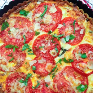 Southern Tomato Pie is a classic summertime dish. Layers of tomatoes, cheese, pesto, herbs and onions are baked in a flaky crust for a savory pie that's downright scrumptious.