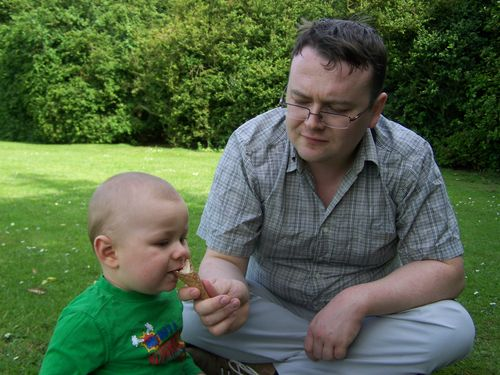TJ feeding Little Man an ice cream cornet whilst sitting on the grass together
