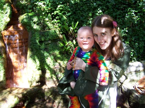 Amanda and Little Man in the shade beneath some trees, both smiling