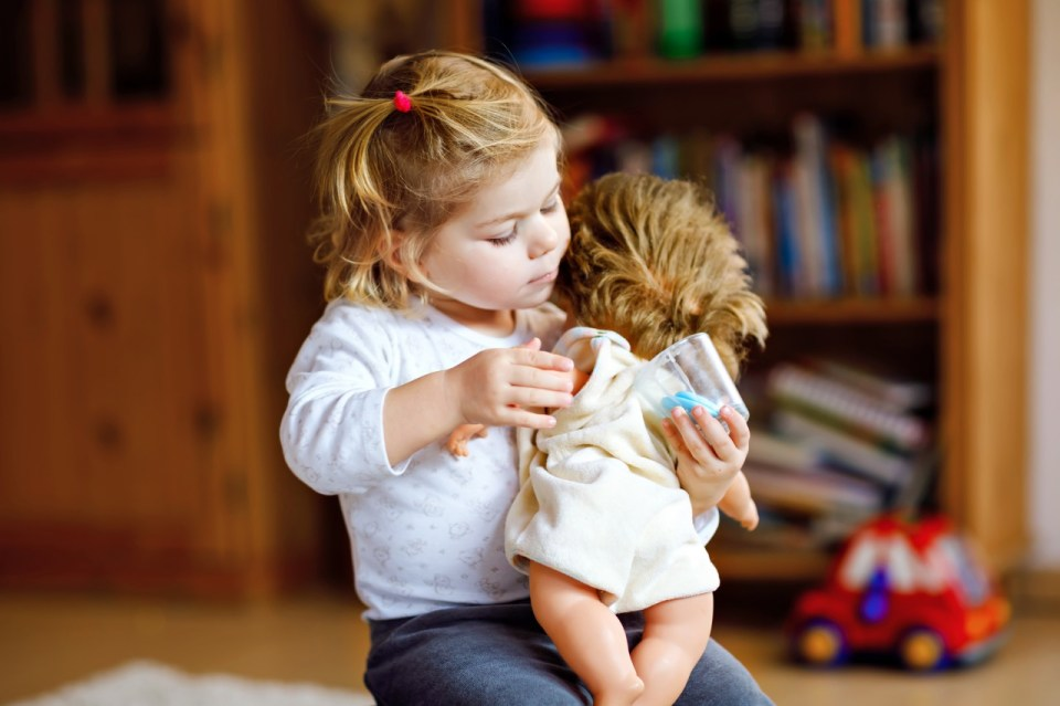 image of a young girl hugging her doll