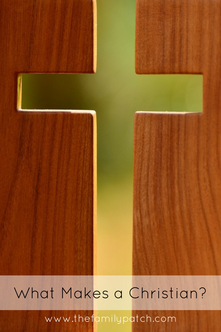"Image of Cross cut out of a wooden block, showing green light behind. The words, ""What Makes a Christian"" are written across the bottom of the image."